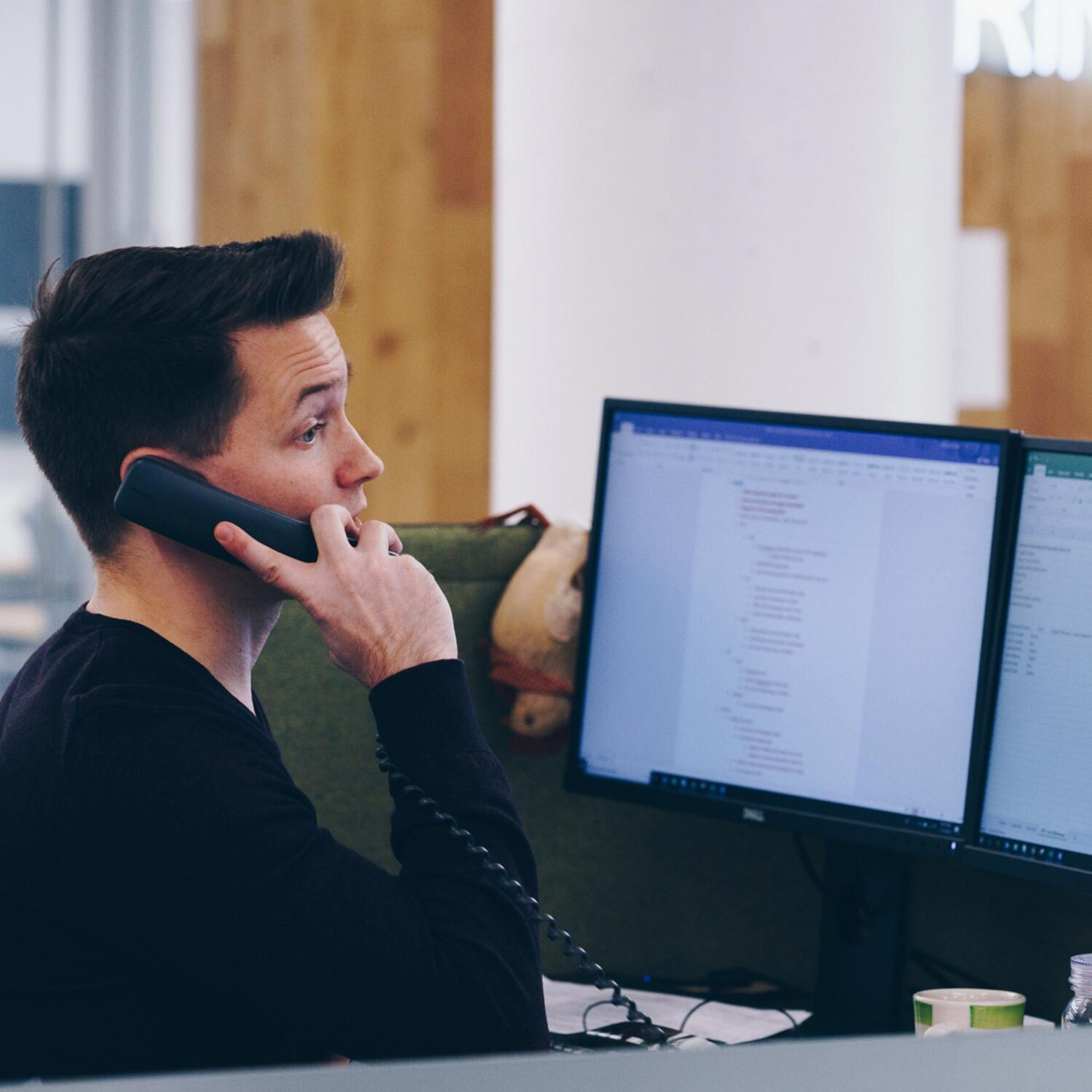 A BellRing employee at a desk, talking on a phone.